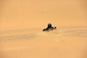 Bodyboarding down the dunes in Swakopmund, Namibia