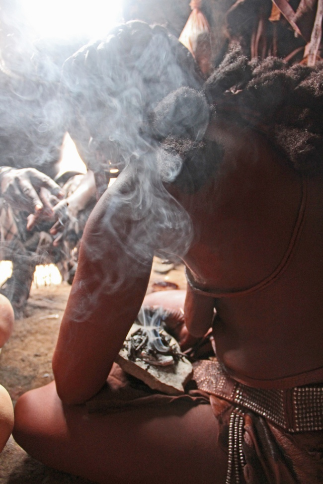 A Himba woman in traditional dress burns myrrh resin as perfume. Kunene, Namibia