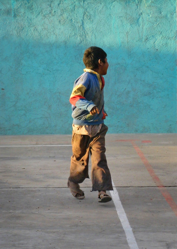 An Aymara boy runs in the sunlight in Uyuni, Bolivia