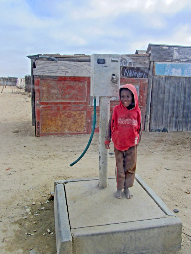 A boy stands by a water pump in Swakopmund, Namibia